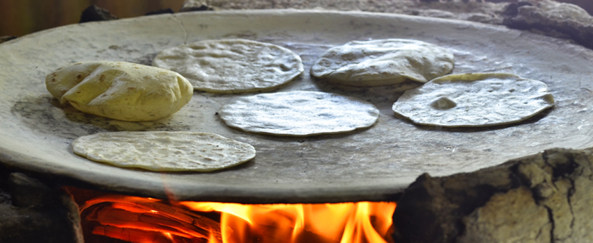 mexican comal over an open fire with tortillas